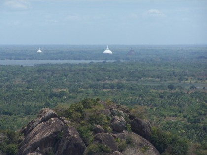 Stupas at Anuradhapura, a view from Mihintale: to the far left is Mirisavatiya stupa; at the center is Ruwanweliseya stupa; to the right, the blurred image is that of Jetavana Stupa.